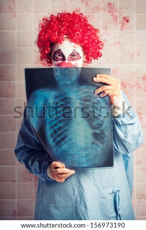 Scary clown doctor peeking behind an x-ray with evil Halloween smile. Funny bones