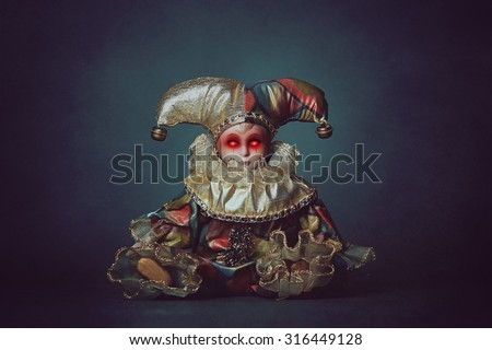 Scary clown doll with demonic eyes . Horror and halloween - stock photo