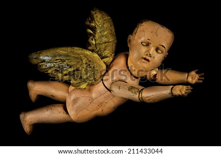 Scary creepy doll with old vintage Halloween trick or treat angel ghoul baby wings on black. - stock photo