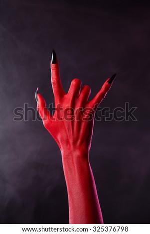 Scary devilish hand showing heavy metal gesture, studio shot on smoky background  - stock photo