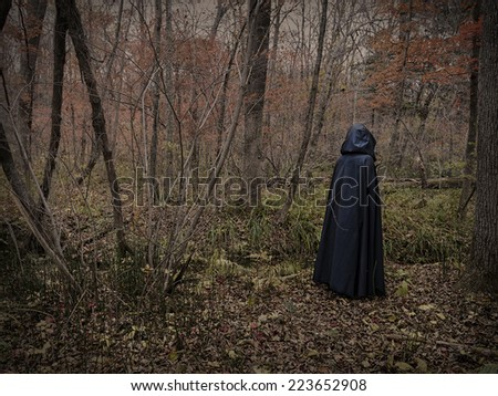 Scary figure in black mantle in the forest, desaturated image - stock photo