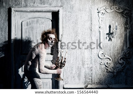 Scary ghost with a candlestick in the old house - stock photo