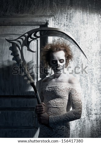 Scary ghost with a scythe in the old house - stock photo