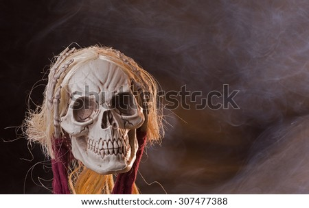 Scary grim reaper skull on a smoky background - stock photo