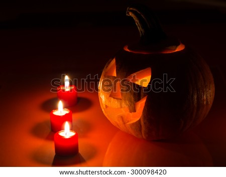Scary halloween carved pumpkin glowing in candlelight - stock photo