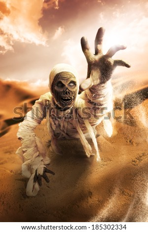 Scary Halloween mummy in hot desert with dramatic lighting - stock photo