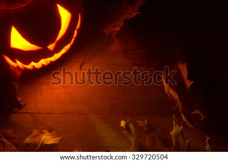 Scary halloween night with spooky evil face of jack o lantern in the corner with red shadows on the wooden surface - stock photo