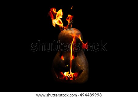 scary Halloween pumpkin is spewing fire flame isolated on black background
