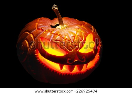 Scary Halloween pumpkin with burning eyes, isolated on black - stock photo