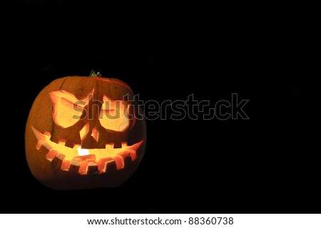 Scary Halloween pumpkin with carved face on black background
