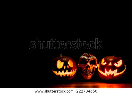 Scary Halloween pumpkins and skull isolated on a black background with room for text. Scary glowing faces trick or treat - stock photo