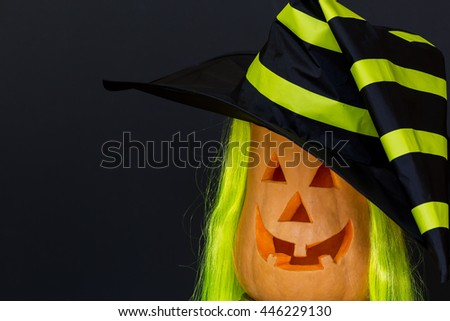 Scary Halloween pumpkins in hat, black background. - stock photo