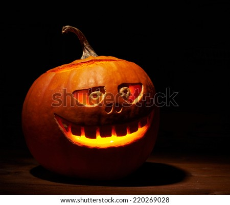 Scary jack o lantern Halloween pumpkin glowing from the inside and placed over the wooden boards surface, composition in a low key dramatic lighting - stock photo