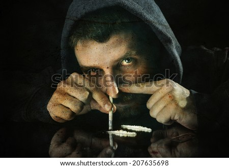 scary looking young drug addict man on hood alone sniffing and snorting cocaine lines with rolled banknote on mirror posing with sick red eyes in moody and grunge lighting studio setting - stock photo