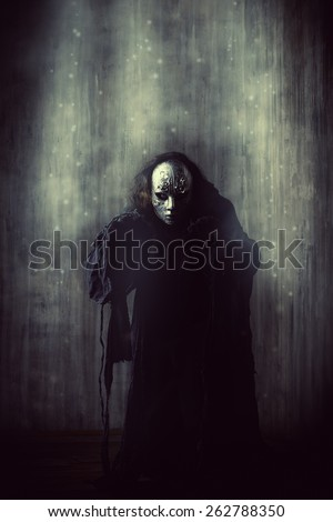 Scary man in iron mask and black robe. Fantasy. Halloween. - stock photo