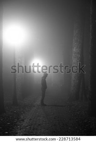 Scary man standing in a lane on a foggy night. Black and white. - stock photo