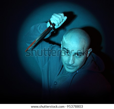 scary man with knife illuminated by a blue spotlight