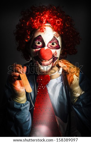 Scary medical clown doctor about to perform oral examination on victim with hand light and tongue depressor. Madness in medical torture