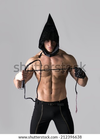 Scary muscular young man with pointed hood on naked body, holding whip in hand - stock photo