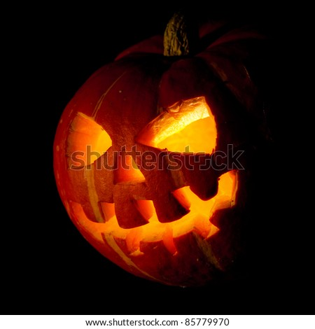 Scary old jack-o-lantern on black background. - stock photo