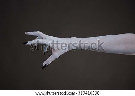 Scary pale skin hand with black nails, body art for Halloween  - stock photo