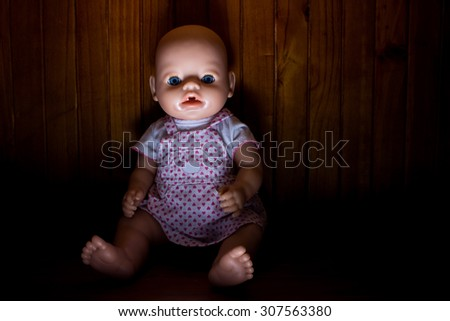 Scary photo of a doll lit from below and with heavy shadow to create atmosphere with a wooden background. - stock photo