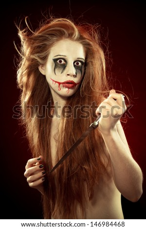 Scary portrait of an angry woman with a sharp knife bathed in the blood - stock photo