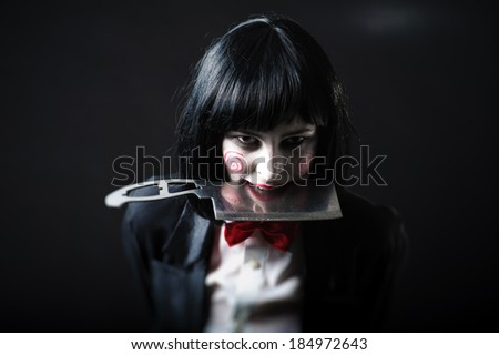 Scary portrait of an angry woman with a sharp knife bathed in the blood. one strange young woman killer holding bloody knife. Halloween. Criminal woman in vintage black coat with an ax in his hands