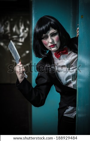 Scary portrait of an angry woman with a sharp knife bathed in the blood. one strange young woman killer holding bloody knife. Halloween. Criminal woman in vintage black coat with an ax in his hands - stock photo