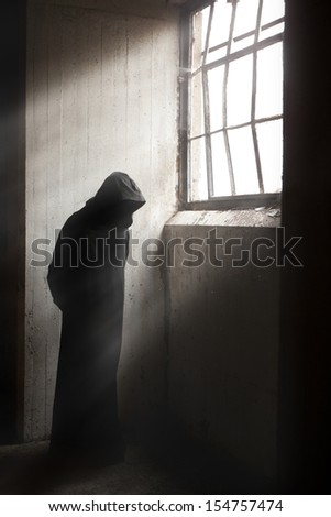 Scary Reaper waiting in a dark abandoned building - stock photo
