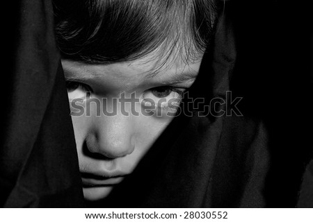 Scary scared little child face in black robe. B/W photograph.