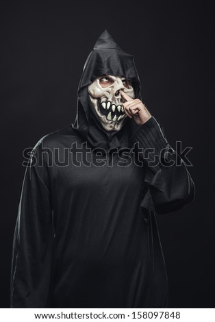 scary skeleton in a robe picks his nose