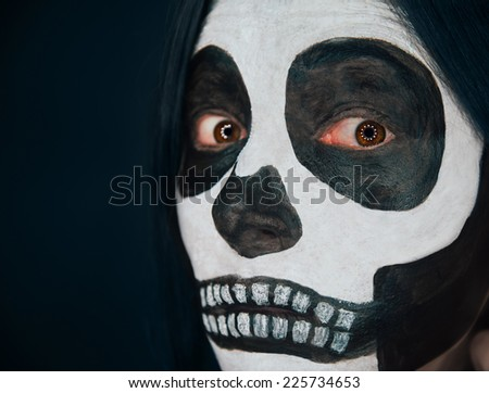 Scary skull woman looks at camera, Halloween makeup