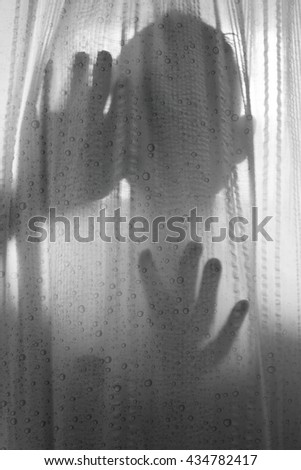 scary person silhouetted against shower curtain