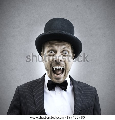 Scary vampire businessman screaming and showing fangs in vintage elegant outfit. - stock photo
