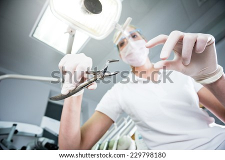 Scary wide shot of beautiful doctor inspecting patient and holding pliers for pulling out the tooth. Young dentist in the cabinet. View from patient's eye. Color toned image. - stock photo