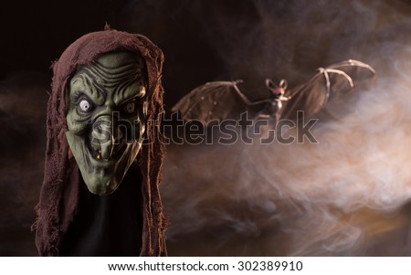 Scary witch head halloween prop with a smoky background - stock photo