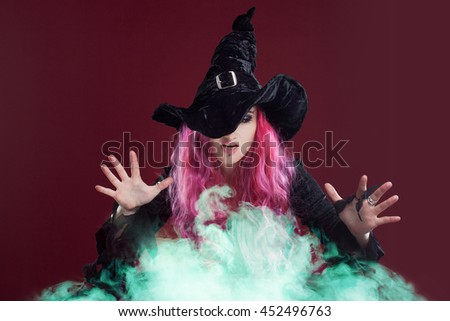Scary witch with red hair performs magic over the green smoke . Halloween, horror theme.