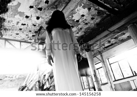 Scary woman in the abandoned hotel - stock photo