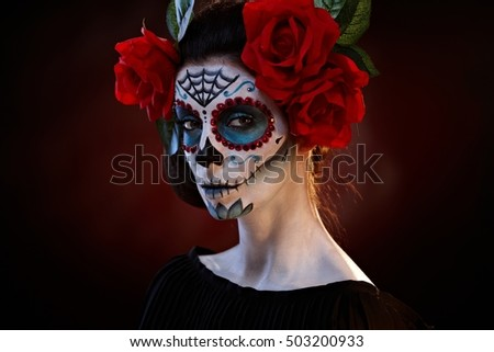 Scary woman wearing santa muerte makeup at halloween.
