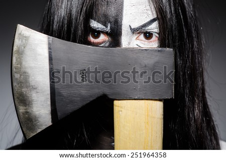 Scary woman with metal axe in halloween concept - stock photo