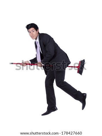 Scary young businessman flying a broom (isolated on white) - stock photo
