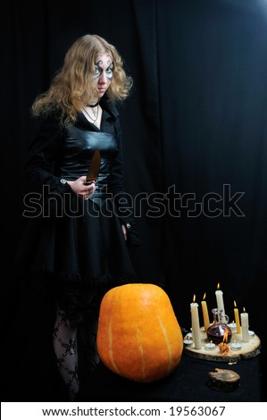 Scary young girl prepares for halloween, on black background