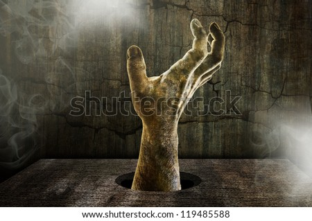 scary zombie hand coming out of a table - stock photo