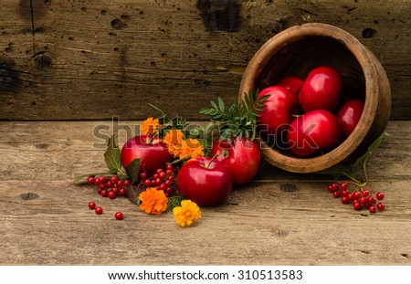 scattered apples in a ceramic pot on a wooden background
