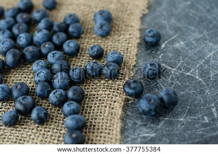 Scattered blueberries on jute tablecloth and scratched black background - stock photo
