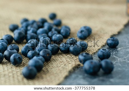 Scattered blueberries on jute tablecloth and scratched black background close up