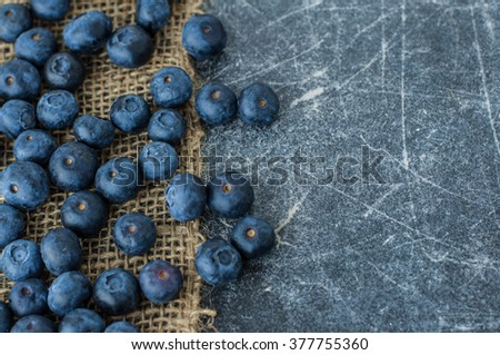 Scattered blueberries on jute tablecloth and scratched black background close up space for text - stock photo
