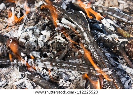 Scattered broken smoldering bonfire with flame top horizontal view