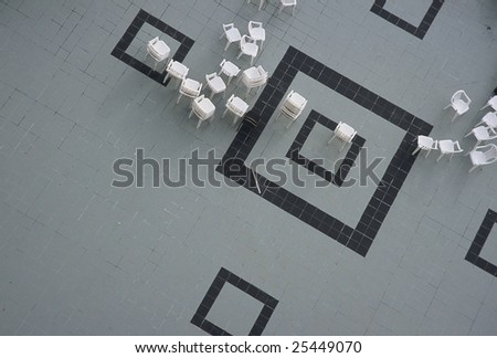 scattered chairs along square pattern tile